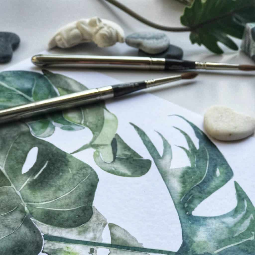 printed artwork of leaves and silver paintbrush